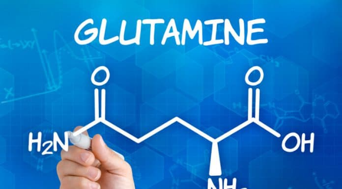 hand-with-pen-drawing-the-chemical-formula-of-glutamine