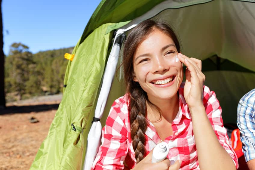 woman outside tent applying sunscreen to her face